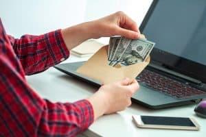 Man opening her salary envelop