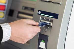 Male hand businessman inserts credit card into the ATM Taking Cash Advance